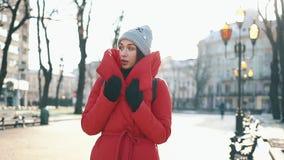 一件红色夹克的美丽的妇女在用雪盖的街道上站立在一个晴朗的冬日 股票视频