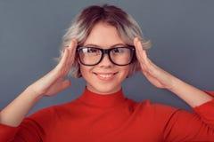 一件红色女衬衫的少妇在灰色墙壁佩带的镜片 免版税库存照片