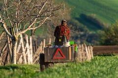 一件红色方格的衬衣乘驾的一位农夫沿在一个绿色领域中的路在用工具和各种各样的Utens装载的一台小拖拉机 库存照片