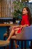 一件红色时髦的礼服的美丽的女孩 免版税库存照片