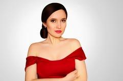 一件红色礼服有光秃的肩膀的和红色唇膏的美丽的女孩在广告首饰的一个浅灰色的背景概念 免版税图库摄影