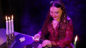 一件红色礼服的一个吉普赛人在烛光的一个不可思议的沙龙在卡片读未来 股票录像