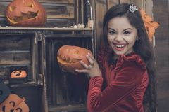 一件红色礼服的一个女孩为万圣夜拿着一盏南瓜灯并且做可怕微笑 库存图片