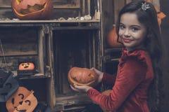 一件红色礼服的一个女孩为万圣夜拿着从一个南瓜的一盏灯 库存照片