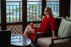 一件红色礼服的一个女孩喝着在旅馆的大厅的一个红色鸡尾酒 太阳镜的一名白肤金发的妇女是 库存图片