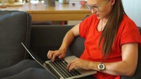 一件红色礼服的一个女孩是与社会网络联系,舒适地坐在一把软的椅子 妇女自由职业者 股票录像