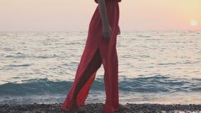 一件红色礼服的一个女孩沿海滨走 股票视频