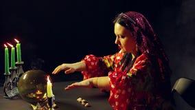 一件红色礼服的一个年轻吉普赛人在与烛光的一张桌上握她的在一个不可思议的球的手 平均计划 股票录像