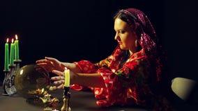 一件红色礼服的一个年轻吉普赛人在与蜡烛的一张桌上调查一个玻璃球并且带领她的在它的手 平均 影视素材
