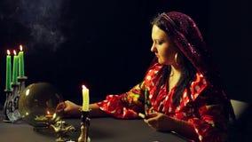一件红色礼服的一个年轻吉普赛人在占卜桌光蜡烛 平均计划 股票视频