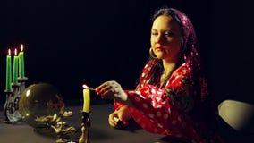 一件红色礼服的一个年轻吉普赛人在桌光蜡烛 平均计划 股票录像