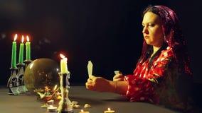 一件红色礼服的一个年轻吉普赛人在烛光的一张桌上在卡片读未来 平均计划 股票视频