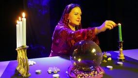 一件红色礼服的一名吉普赛妇女在占卜屋子在一个被雕刻的烛台的光蜡烛 股票录像