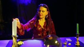一件红色礼服的一名吉普赛妇女在占卜屋子在一个被雕刻的烛台的光蜡烛 影视素材
