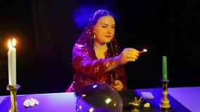 一件红色礼服的一名吉普赛妇女在占卜屋子在一个被雕刻的烛台的光蜡烛 股票视频