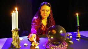 一件红色礼服的一名吉普赛妇女在占卜屋子在桌上的光蜡烛 股票视频
