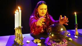 一件红色礼服的一名吉普赛妇女在占卜屋子在桌读在镜子球的未来 股票录像