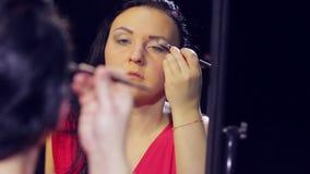 一件红色礼服的一名年轻深色的妇女在镜子前面做与轻的树荫的眼睛构成与刷子 股票录像
