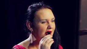 一件红色礼服的一名年轻深色的妇女绘她的有明亮的红色口红的嘴唇 股票录像