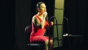 一件红色礼服的一年轻女人在镜子前面应用在她的嘴唇的明亮的红色口红 影视素材