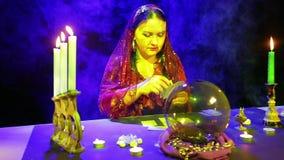 一件红色礼服的吉普赛人在围巾计划在蜡烛的反射的卡片 股票视频