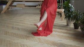 一件红色礼服的美丽和性感的怀孕妇女有坐摇摆和摇摆的黑发的 股票视频