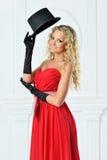 一件红色礼服的美丽的妇女有帽子的。 免版税库存照片