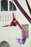 一件红色运动服的女性空气体操运动员执行在空中丝绸的一锻炼 免版税库存图片