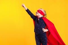 一件红色雨衣和面具的滑稽的矮小的力量超级英雄儿童女孩 超级英雄概念 免版税图库摄影