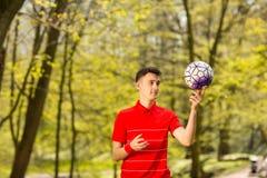 一件红色T恤杉的一年轻人使用与一个足球在绿色公园 r 免版税库存照片
