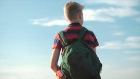 一件红色T恤杉的少年有在他的一个背包的,在日落,坐高小山,享受自然,自由 股票录像