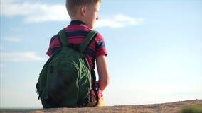 一件红色T恤杉的少年有在他的一个背包的,在日落,坐高小山,享受自然,自由 股票视频