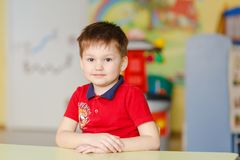 一件红色T恤杉的男孩坐在一张书桌在幼儿园 库存照片