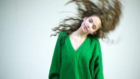 一件绿色毛线衣的一个卷曲女孩振翼她的头发 冬天衣裳的巴黎人女孩 时尚神色和秀丽概念 影视素材