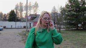 一件绿色毛线衣的一个女孩是在城市和谈话在一个手机的郊区 照相机移动与她 影视素材