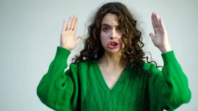 一件绿色毛线衣的卷曲女孩有括号的关闭她的面孔用她的手并且显示各种各样的情感 巴黎人女孩 影视素材