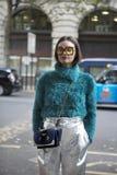 一件绿色毛茸的毛线衣的美丽和时髦的A女孩由摆在伦敦时尚星期期间的虚假毛皮制成 外部Eudon崔 库存图片