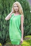 一件绿色短的夏天礼服的美丽的白肤金发的女孩在城市的街道上 免版税库存照片