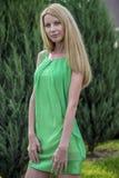 一件绿色短的夏天礼服的美丽的白肤金发的女孩在城市的街道上 图库摄影