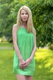 一件绿色短的夏天礼服的美丽的白肤金发的女孩在城市的街道上 库存照片