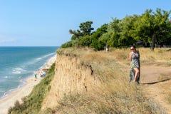 一件绿色礼服的一名英俊的妇女是在高海边上 库存图片