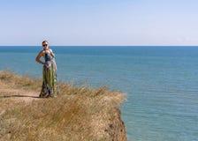 一件绿色礼服的一名英俊的妇女是在高海边上 免版税库存照片
