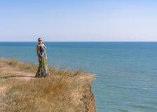 一件绿色礼服的一名英俊的妇女是在高海边上 库存照片