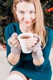 一件绿色礼服的美丽的女孩有一个杯子的在他的手上 免版税库存图片