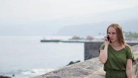 一件绿色礼服的美女谈话在江边的电话身分在海洋和微笑附近 股票录像