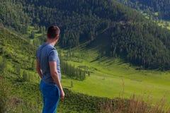 一件绿色T恤杉的人站立在后方的峭壁边缘他是山和绿色树一个五颜六色的看法  免版税库存照片