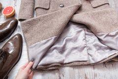 一件羊毛外套的衬里在妇女` s手上 时兴的概念 免版税库存图片