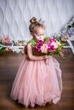 一件美丽的桃红色礼服的一位小公主嗅牡丹、木兰、莓果和绿叶花束对白色墙壁和f 免版税库存图片