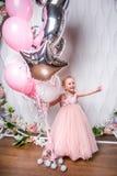 一件美丽的桃红色礼服的小公主拿着气球、笑和点对边,轻的背景 免版税库存图片