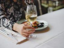 一件美丽的礼服的一个女孩在一家美丽的餐馆吃着一个可口海鲜盘 完善的时间,鲜美食物 库存照片